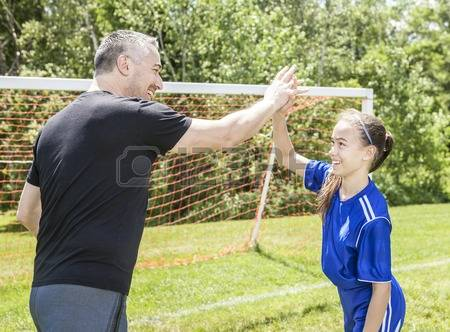 Father playing soccer with his daughter