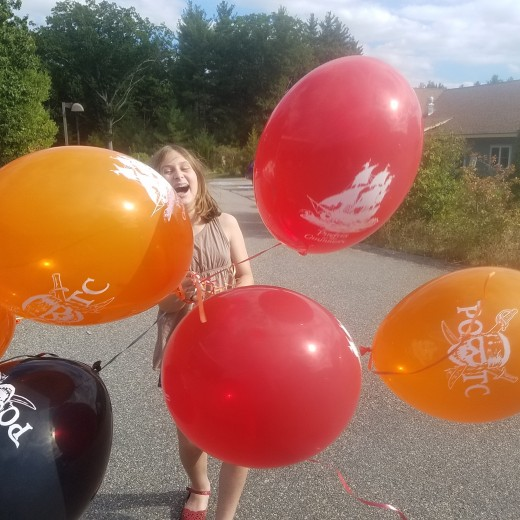 My daughter in fits of laughter as her balloons flew in every direction as she brought them home on a windy day.