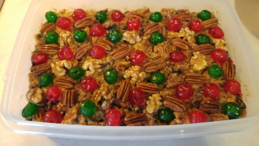 Place red and green cherries around the top, and add pecans and walnuts between them.