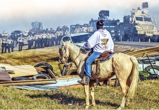 A lone tribesmen sitting on his trusted stead looks upon the approaching, opposing forces one day during the many long months of protesting the Dakota Pipeline and the effects it will have on the surrounding people, land and water.