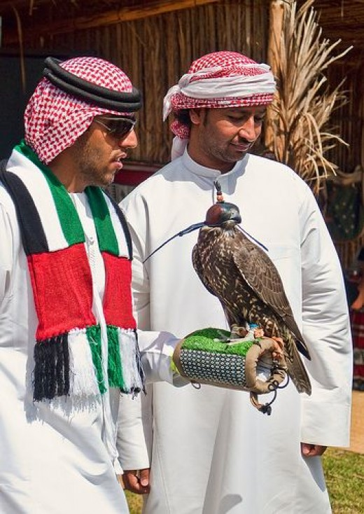 Falconers from the United Arab Emirates and wearing the traditional dress of UAE