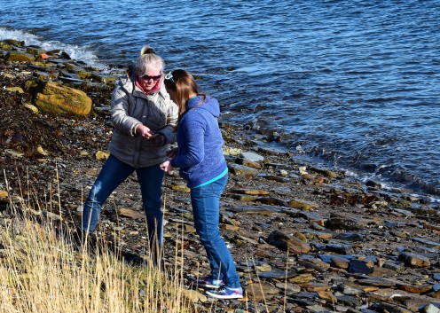 Mother and daughter compare beachcombing finds.