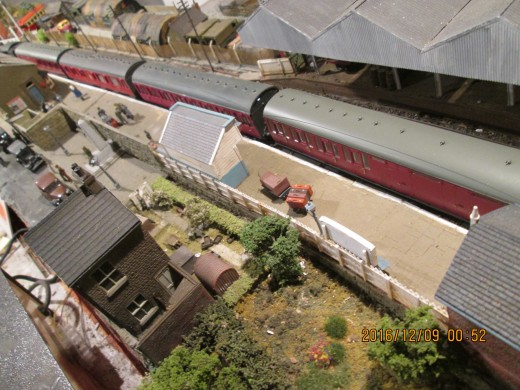 The same train from a different angle overlooking the station from the field, showing luggage on trolleys awaiting collection (between the open-fronted shelter and signal cabin)