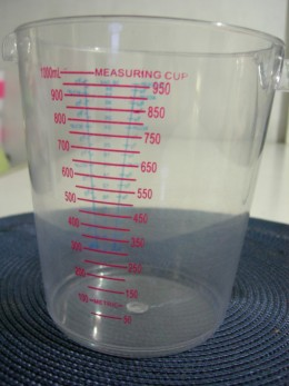 Plastic graduated measuring cup with cup measurement gradation and its equivalent in milliliter gradation.