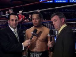 Matt Godfrey is being interviwed after a victory by Joe Tessitore, left, and Teddy Atlas, far right.