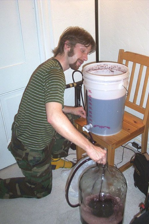 Racking red wine. i.e. siphoning the liquid from primary fermentation vessel to secondary fermentation vessel (carboy), which removes most of the lees (solids) from the liquid.
