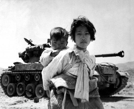 With her brother on her back a war weary Korean girl tiredly trudges by a stalled tank