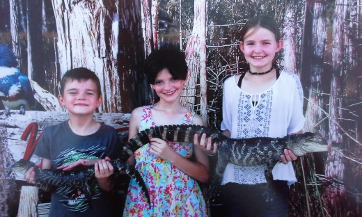 Our three kids at a fair where they got to hold a baby aligator