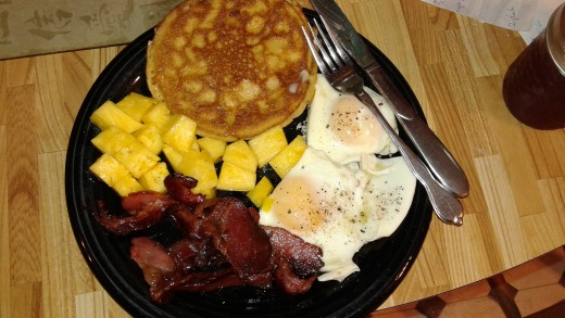 Homegrown bacon and eggs, with a pancake waiting for chokecherry jam