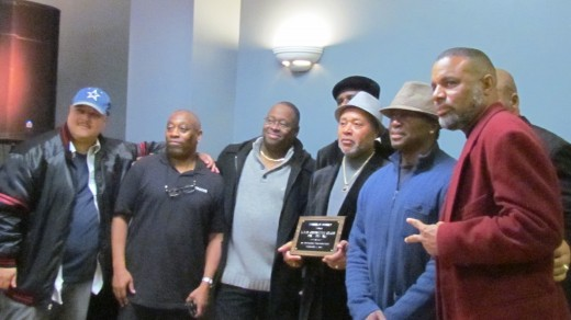 Teddy Robinson, gather with other band members and friends of Traxx9 Band with a plaque presented to the band.