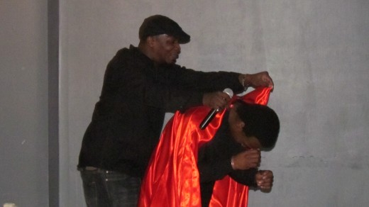 Larry Snow, puts a cape on Hashim Wilson, who did an amazing dance during one of the performances.