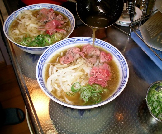Assembling Vietnamese Pho soup for serving, by pouring the hot stock over the meat, herbs, noodles and vegetables.