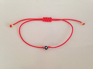 A red string with the Evil Eye on it, which is used as a talisman.