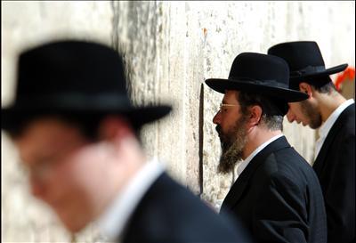 Orthodox Jewish men praying at the Western wall