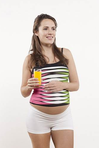 A beautiful pregnant woman holding a glass of orange juice