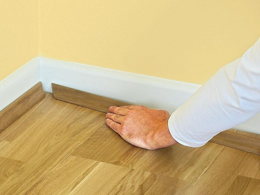 Fixing floor trim (baseboard) as a finishing touch.