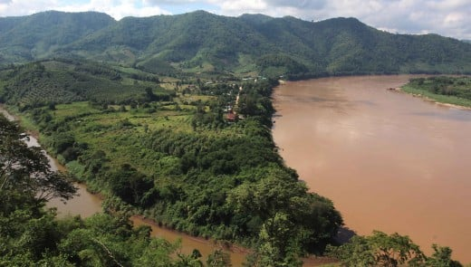 One of the great landmark vistas. The big river is the Mekong, and the smaller river is the Hueang, which forms the Thai-Laos border west of this point. Virtually all the scenery in the photo therefore, is in the nation of Laos.