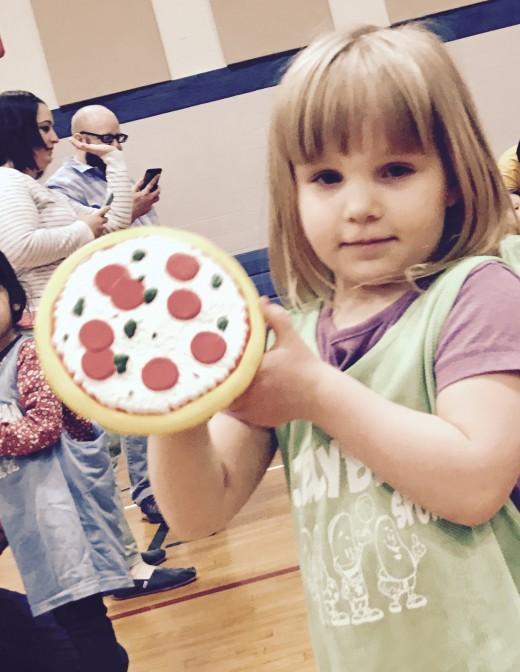 Girl holds foam pizza
