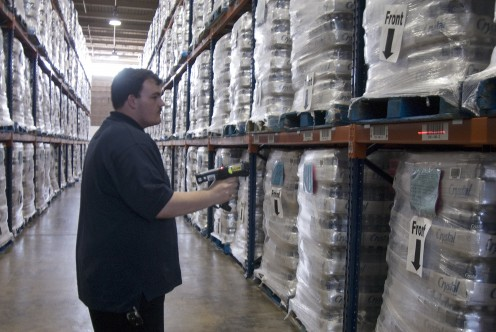 A lone warehouse worker takes an inventory with a bar code scanner.