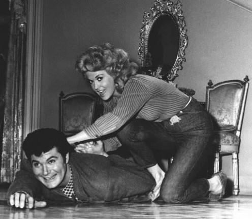 """Max Baer, Jr., """"Jethro,"""" and Donna Douglas, """"Ellie Mae,"""" wrestle on mansion floor."""