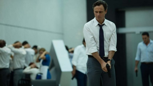 Barry (Tony Goldwyn) holding a gun while the employees face the wall.