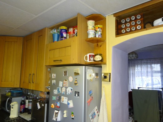 Bespoke corner shelving at the end of wall unit for display of decorative cups.