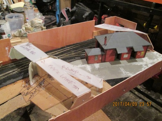 Plastic cut to approximate shape is tacked onto the formers to show where the road overbridges and embankments will go