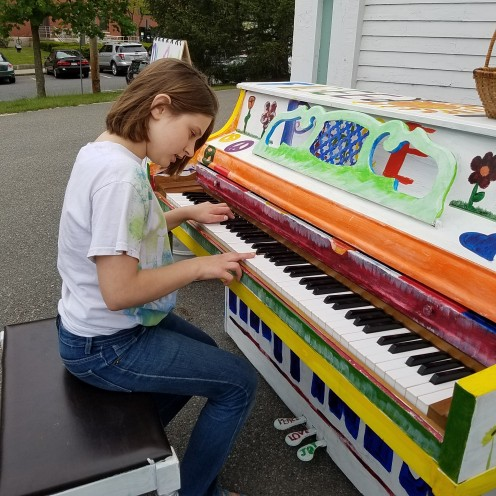 Author's daughter playing an original composition on the piano in front of our UU church.