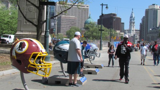 Visitors took photographs in the midst of the large helmet for individual teams. Young and old found this display outside of the entrance to NFL Draft.