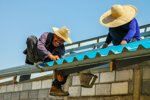 Two men installing roofs for a house.
