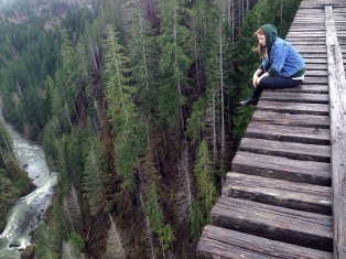This girl is lonely. How can we tell? Only lonely people would dare fate and sit on a working railroad bridge.