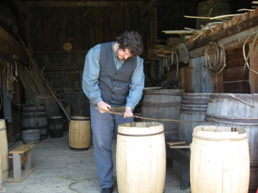 A cooper at work on a barrel in a historic village museum.