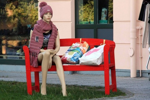 A display doll is set up on a bench with her shopping bags appearing to be waiting for a bus for transportation.