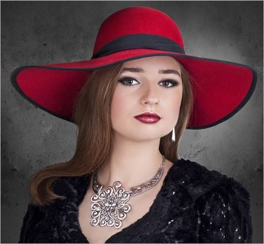 Chic wide brimmed red hat with black trim.