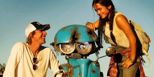 Mark Wahlberg with an Autobot posing with Isabela Moner. Mark Wahlberg Stars as Cade Yeager, along with Isabela Moner, who plays Izabella. The blue-green robot seen is Squeaks, an Autobot..