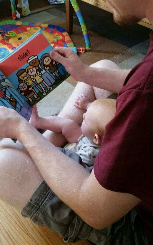 Reading on Dad's lap.