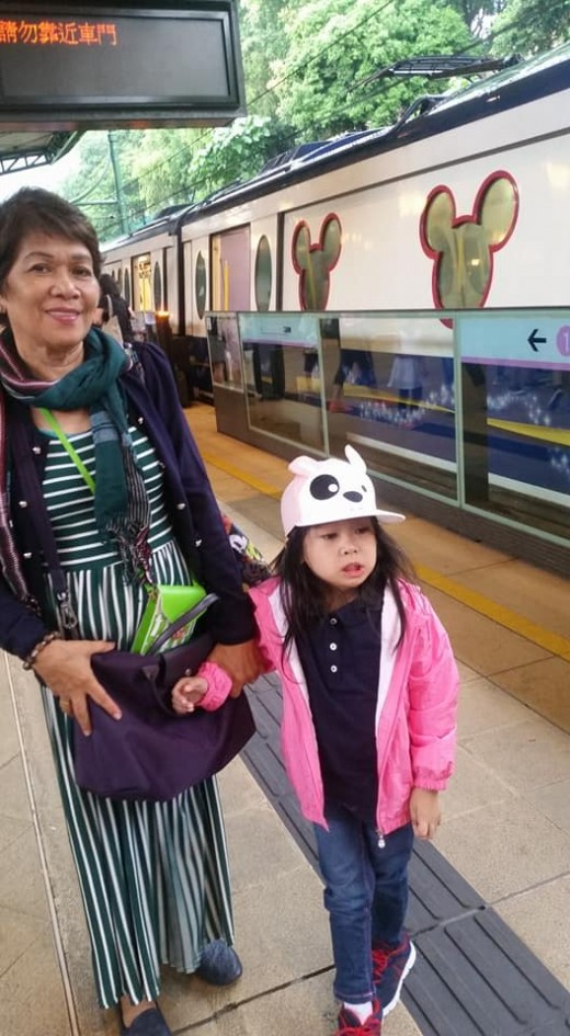 My daughter and her grandma with the train in the background