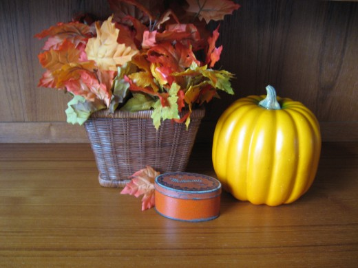 This grouping of a basket with faux fall leaves, a pumpkin, and a vintage tin are on the sideboard in the dining room.