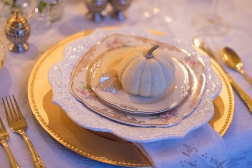 Isn't this table setting elegant! The miniature white pumpkin, layered plates, and ribbon in shades of cream look lovely, yet still evoke that autumn feeling.