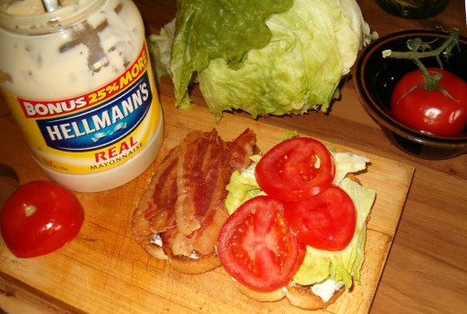 Topping some toast with bacon, lettuce, and slices of tomato.