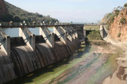 The sluicegates and spillway. The congestion of water hyacynth can be seen at the top of the spillway