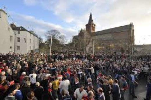 A crowd of players and supporters watch and play in the heart of the town.
