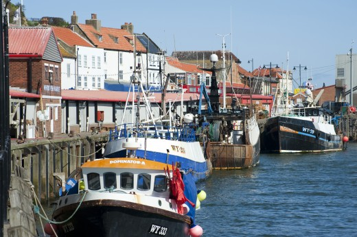 Whitby Harbour in the millennium. Lined up along the quayside are ocean-going vessels as well as inshore boats that would unload crab or lobster and smaller sea fish