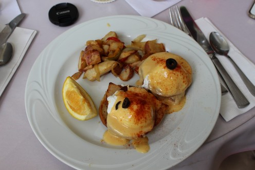This first version of Eggs Benedict has a slice of orange along with home style potatoes.