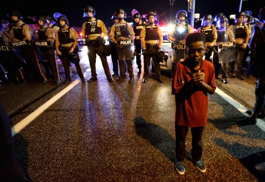 A young boy turns his back to police during a Black Lives Matter protest.