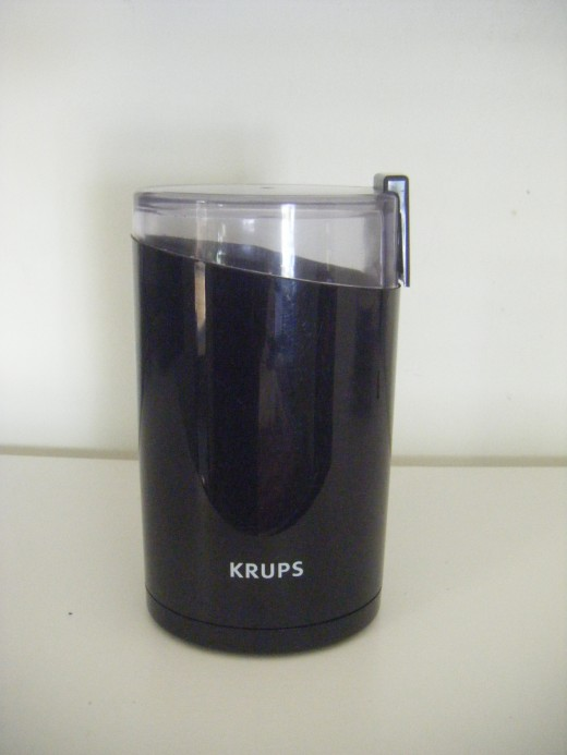 The KRUPS F203 electric blade grinder that I use in my office area.  Blade grinders are usually more affordable than burr grinders, but they tend to be noisier, and less precise. The grinding process involves a spinning blade which chops the beans up