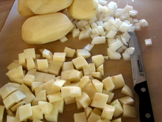 Cubed the potatoes about the size of a large sugar cube and dice the onion about the same size. This is the first step before making three layers in the dish.