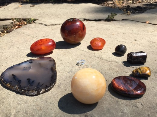 As listed in the table below. Counter clockwise starting at 12 o'clock: three carnelian, dendritic agate, orange calcite, red and brown tiger's eye, kyanite, bloodstone, and Herkimer diamond center.