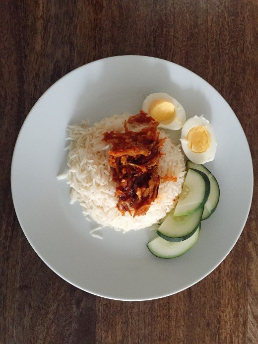 Final result. Nasi lemak is served with sambal ikan bilis, hard-boiled egg and fresh cucumber sliced.