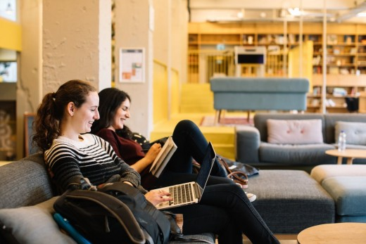 Friends sitting on the couch on their laptop.